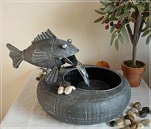 Brunnen mit Fisch aus Metall im Used-Look
