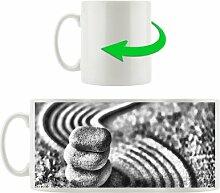 Kaffeebecher Wellenmuster im Sand mit Steinen