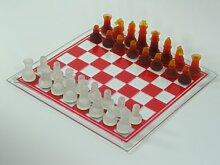 Schachbrett mit Glasfiguren in weiß und rot